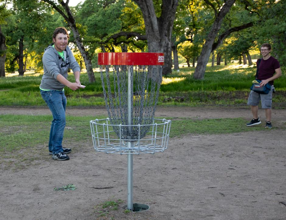 Disc golfer throwing disc to updated disc golf basket.