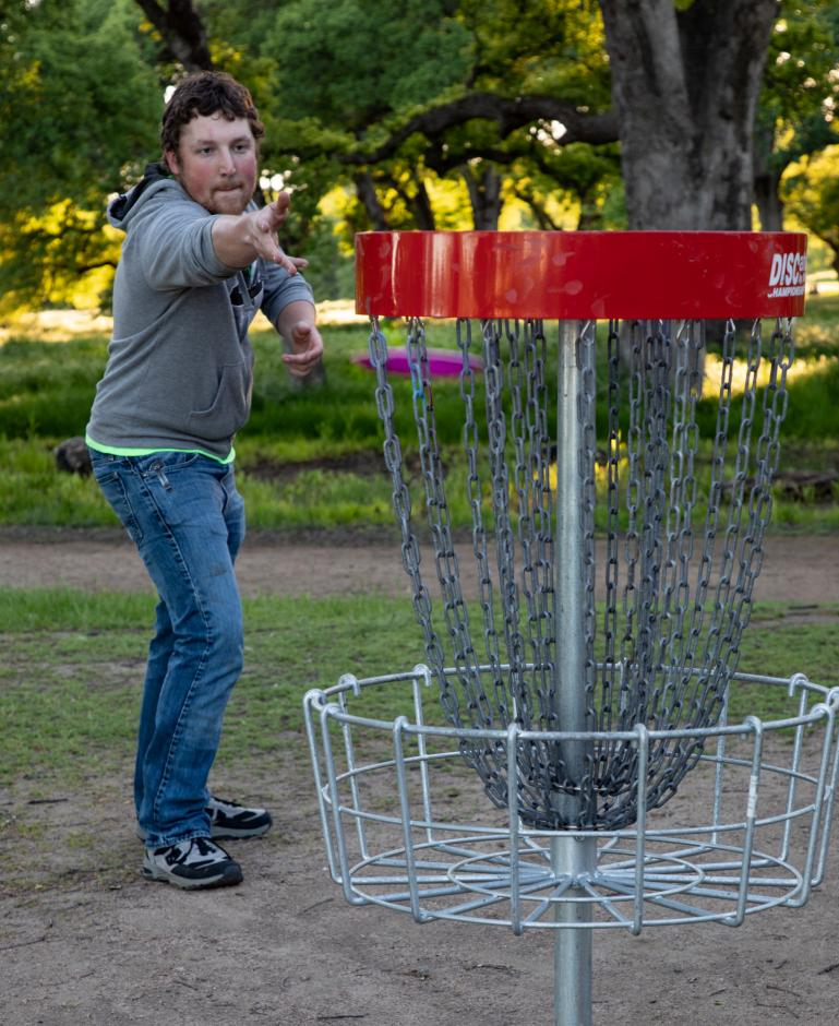 Disc Golfer throwing disc into basket.
