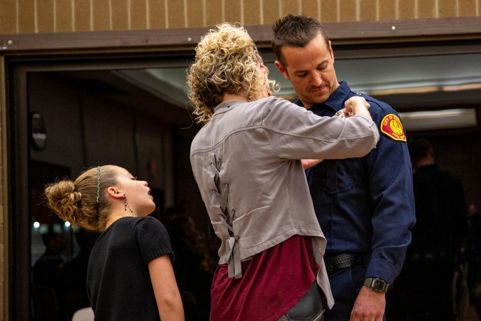 Firefighter recruit Chris Marson is pinned by his wife Alexis and daughter Selah.