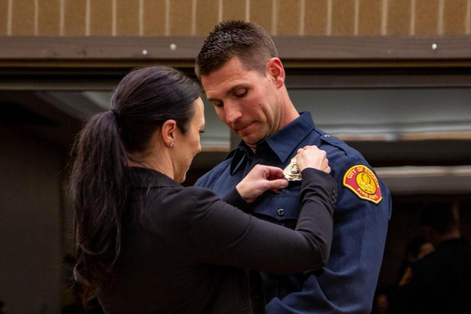 Firefighter recruit Erik Garside is pinned by his wife Amy.