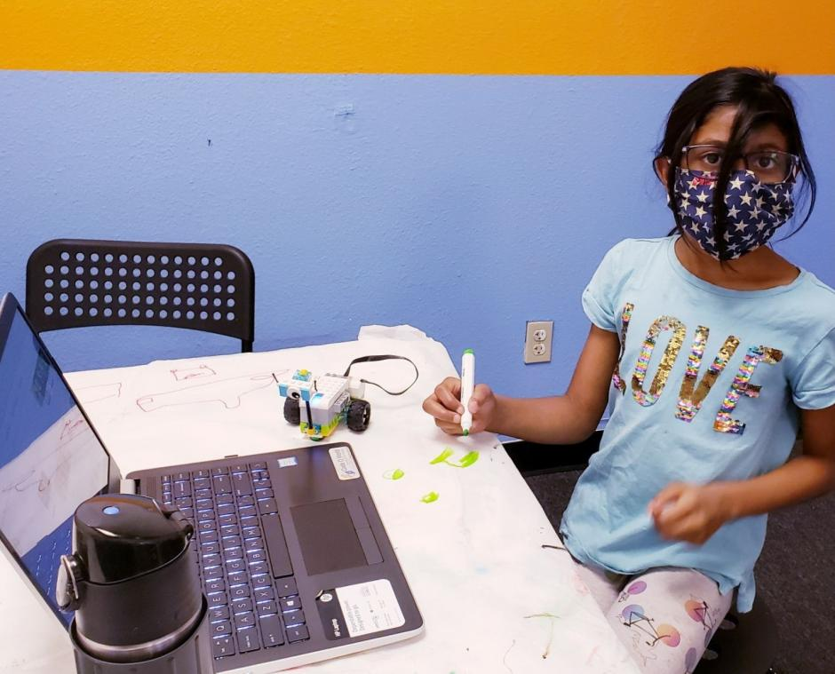 A young girl sits at a desk with a laptop and robot nearby.
