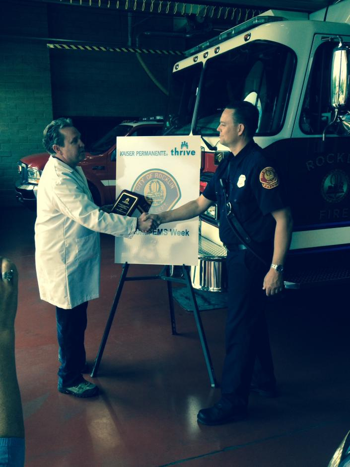 Fireman Wade receiving an EMS award from Dr Morris Kaiser Roseville