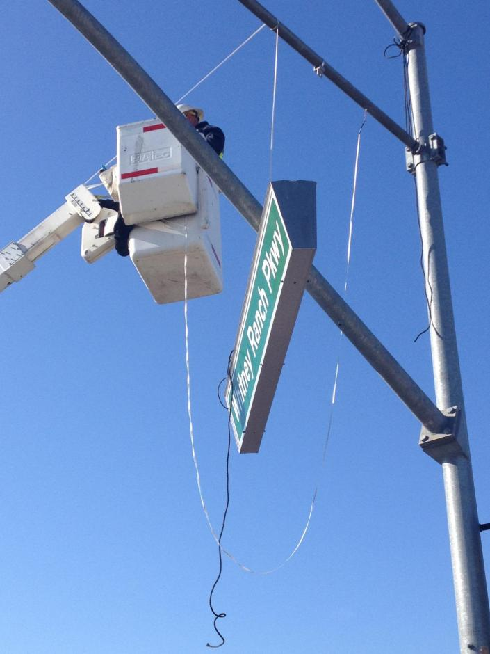 Member of Rocklin's Traffic Division works on a street sign from a crane bucket.