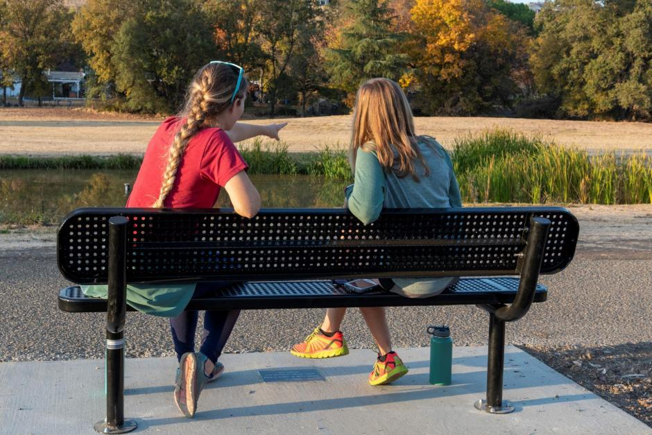 Two park-goers sit on one of the newly installed benches at Sunset Whitney Recreation Area