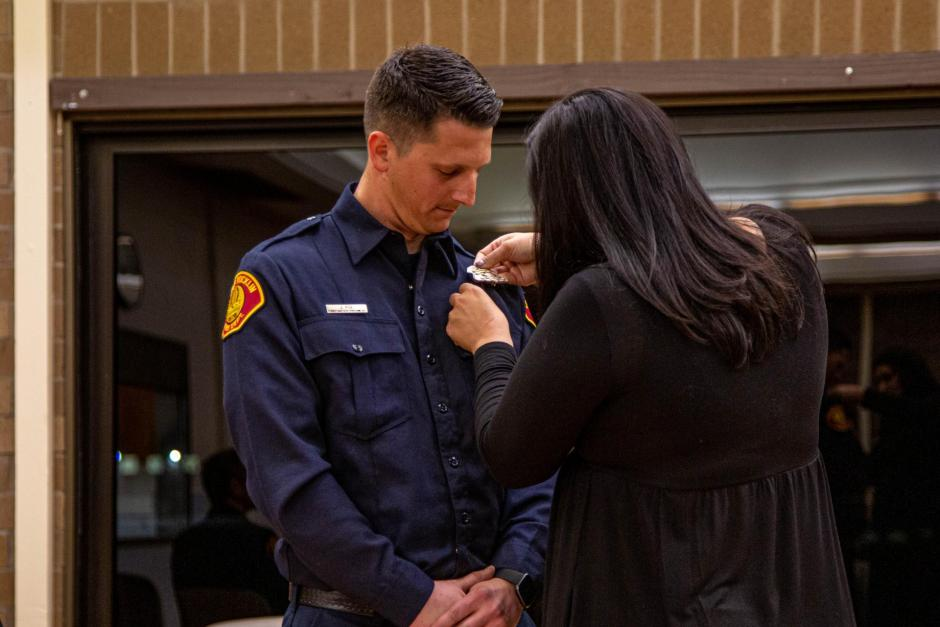 Firefighter recruit Jordan Poe is pinned by his wife Anna.