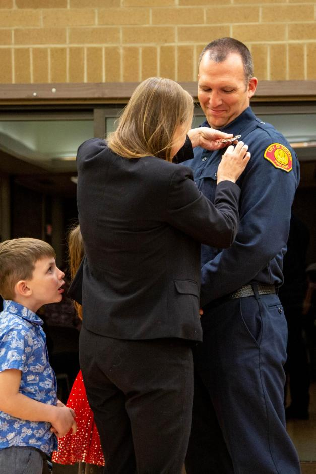 New firefighter recruit Kevin Stenson is pinned by his wife Jacqui, daughter Ryleigh, and son Tyler.
