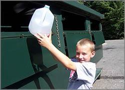 Photo of boy dropping recyclable bottle in bin